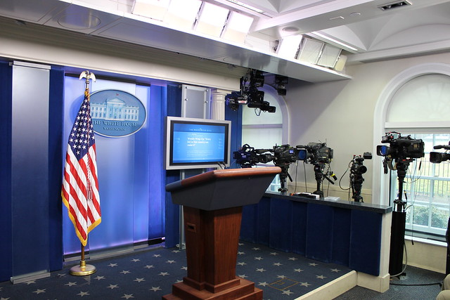 Photo of the White House press briefing room lectern with White House seal and American flag.