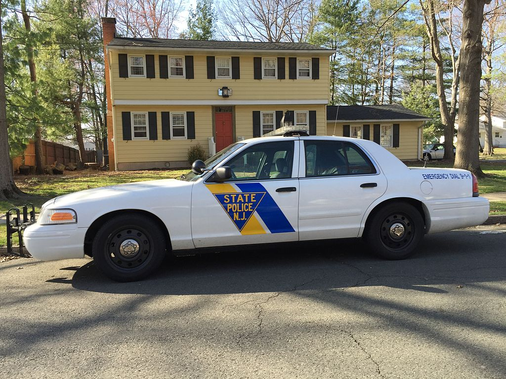 Photo of white New Jersey police department state police car outside a house. Taken from Wikimedia Commons.