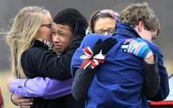 Mourners hug after the burial of Daniel Parmertor at All Soul's Cemetery, Saturday, March 3, 2012, in Chardon, Ohio.
